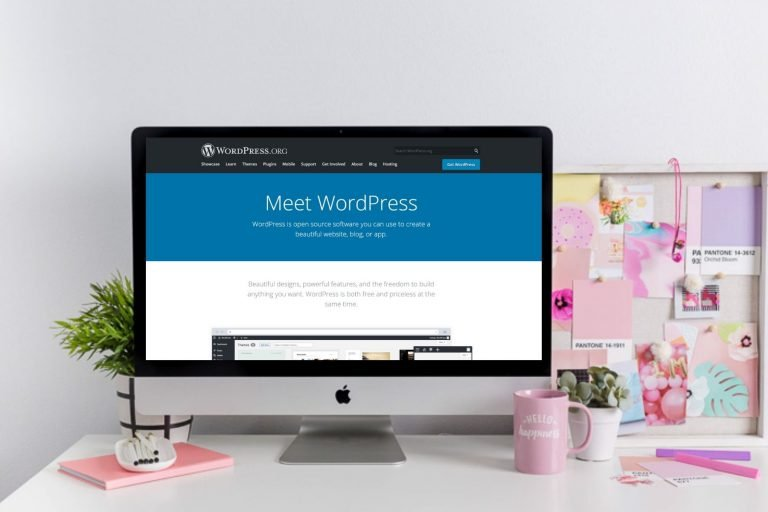 5 Reasons Why Your Website Should be Built Using WordPress a computer on a desk with accessories