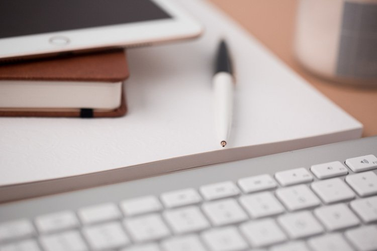 Content The Crucial Component Of Successful Websites a keyboard, ipad, book and pen on a desk with a mug