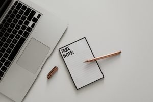 5 Tips for Choosing the Best Website Host a notepad, pen and laptop