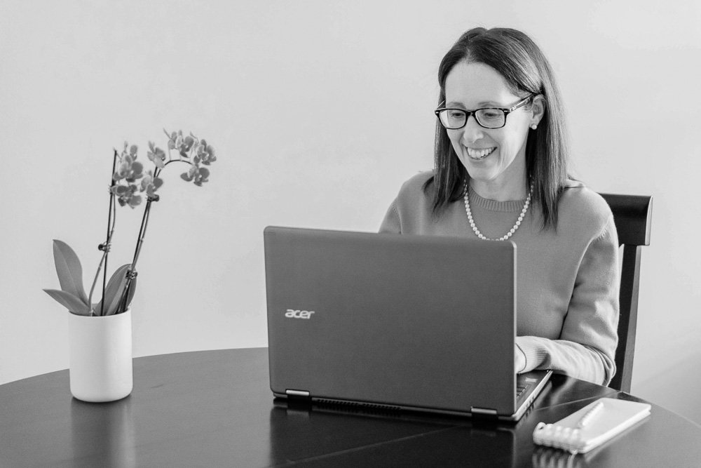 How to design a website black and white photo of Robyn White of RDW Design Studio smiling and sitting at a desk with a laptop