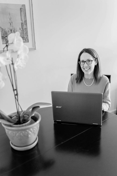 Website Design Services black and white photo of Robyn White of RDW Design Servicese sitting at a desk with a laptop